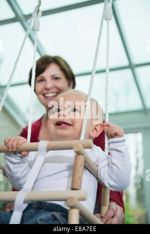 Happy toddler sitting in a swing - Stock Photo