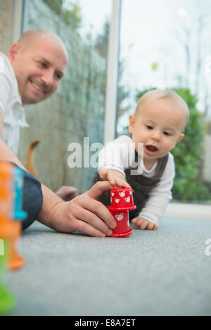 Father and his little son playing together - Stock Photo