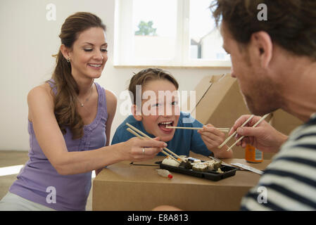family sitting eating Sushi new apartment boxes - Stock Photo