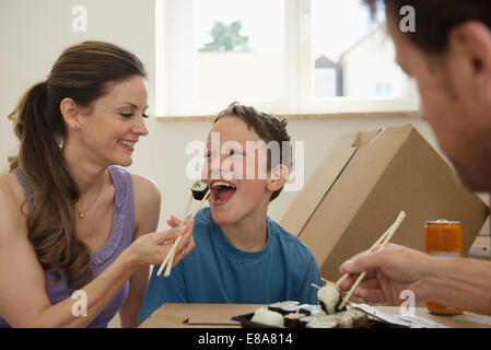 New home moving in family eating sushi - Stock Photo