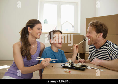 Moving in transport young family eating sushi - Stock Photo