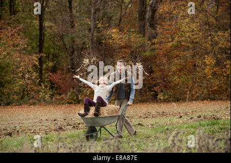 Father pushing happy daughter in wheelbarrow - Stock Photo
