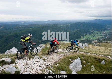 three mountain bikers looking at view, Vipava valley, Istria, Nanos, Slovenia - Stock Photo