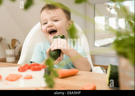Boy eating cucumber in kitchen, smiling - Stock Photo