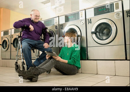 Man and woman are talking in laundry, smiling - Stock Photo