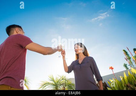 Couple toasting with champagne in penthouse rooftop garden, La Jolla, California, USA - Stock Photo