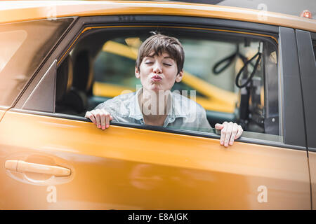 Woman blowing kiss from yellow taxi, New York, US - Stock Photo