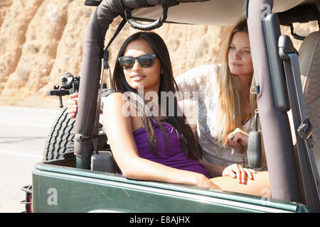 Two young women sitting looking out of jeep - Stock Photo