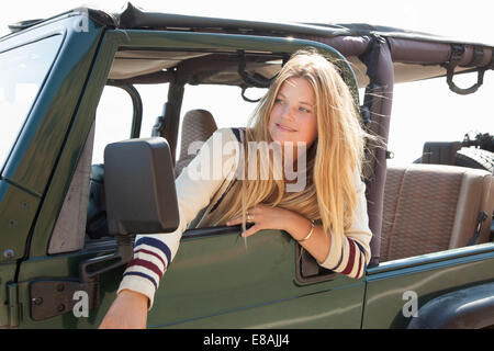Young woman looking out of jeep window - Stock Photo