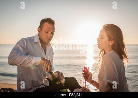Young couple drinking champagne on beach, Castiadas, Sardinia, Italy - Stock Photo
