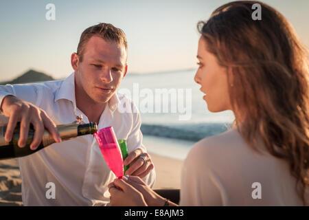 Young couple pouring champagne on beach, Castiadas, Sardinia, Italy - Stock Photo