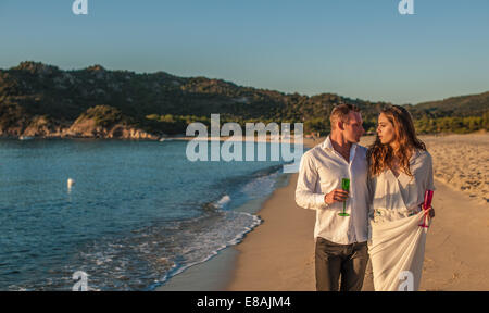 Young couple strolling with champagne on beach, Castiadas, Sardinia, Italy - Stock Photo