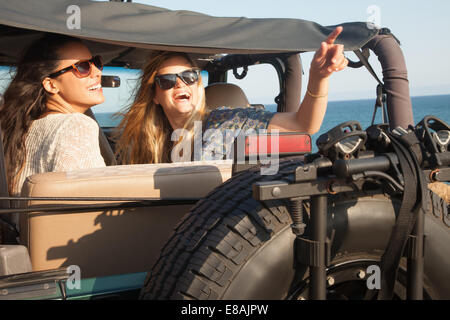 Two young women looking up from jeep at coast, Malibu, California, USA - Stock Photo