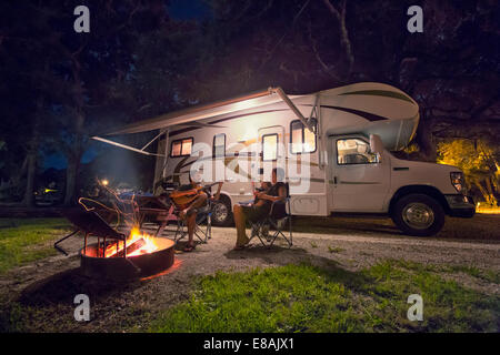 Mid adult couple and baby daughter sitting in front of campfire at night - Stock Photo