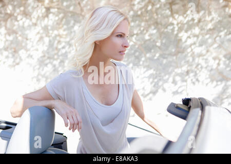 Woman beside her convertible car - Stock Photo