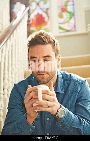 Man with mug on stairs - Stock Photo