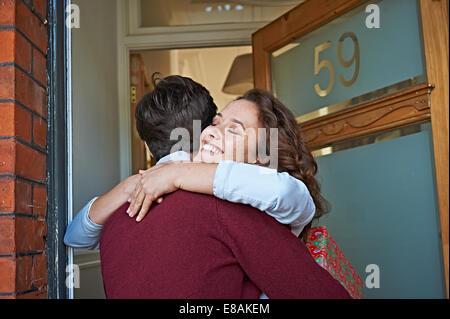 Couple hugging at front door - Stock Photo