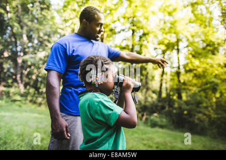 Father and daughter watching with binoculars in forest eco camp - Stock Photo