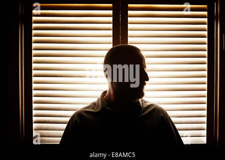 Portrait of silhouetted mature man in front of window blind - Stock Photo