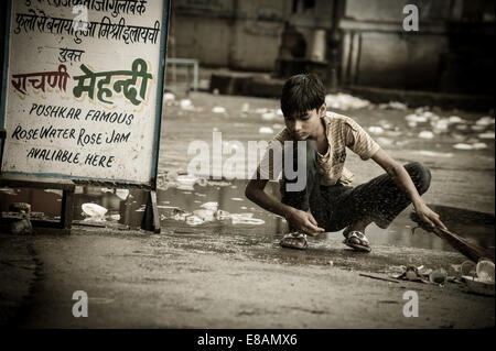 Rural Life in Rajasthan, young boy cleaning the street - Stock Photo