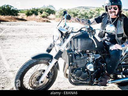 Portrait of male motorcyclist on arid plain, Cagliari, Sardinia, Italy - Stock Photo