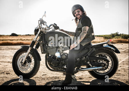 Portrait of mature man on motorcycle on arid plain, Cagliari, Sardinia, Italy - Stock Photo
