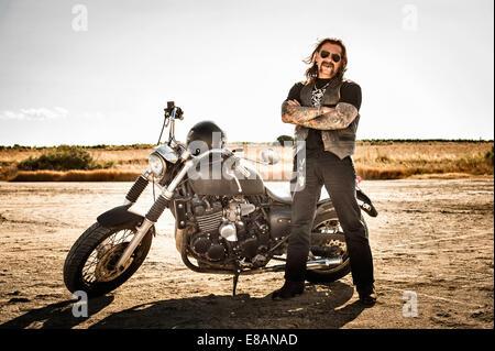 Portrait of mature male motorcyclist on arid plain, Cagliari, Sardinia, Italy - Stock Photo