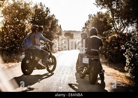 Rear view of four friends on motorcycles chatting on rural road, Cagliari, Sardinia, Italy - Stock Photo