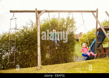 Brother and sister playing on swings in garden - Stock Photo