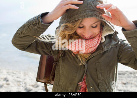 Woman all wrapped up on windy beach - Stockfoto