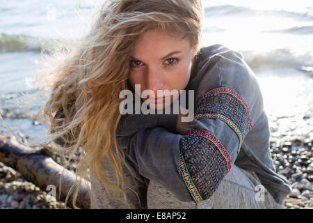 Woman sitting on windy beach - Stockfoto