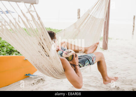 Man enjoying coconut water in hammock on beach - Stock Photo