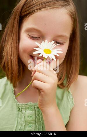 Portrait of girl in garden holding up daisy - Stock Photo