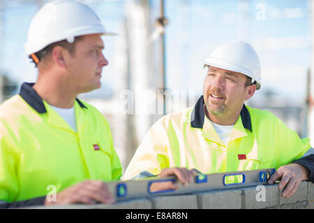 Builder and site manager using spirit level on construction site wall - Stock Photo