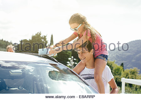 Brother and sister washing car - Stock Photo