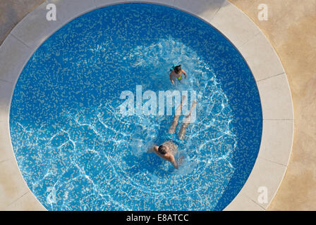 Overhead view of man and toddler daughter in swimming pool - Stock Photo