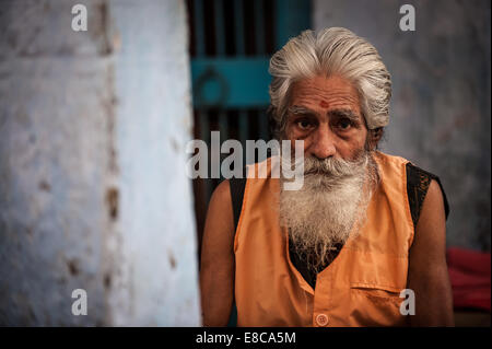 Old Indian man motionless on the roadside with traditional Indian clothes - Stock Photo