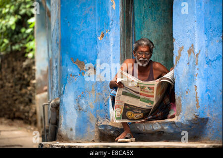 Indian man sitting on his doorstep reading a local newspaper - Stock Photo
