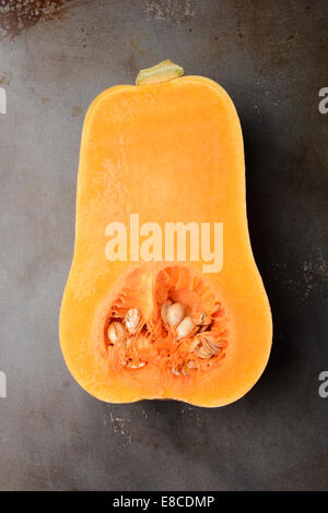 Butternut Squash on a metal cooking sheet. The vegetable is cut in half showing the inside. Vertical format. - Stock Photo