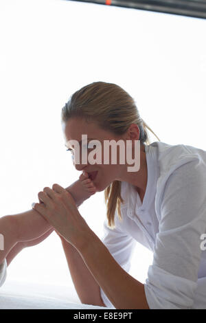 Mother kissing her baby's feet - Stock Photo