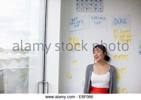 Smiling businesswoman with in front of whiteboard with adhesive notes - Stock Photo