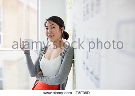 Smiling businesswoman leaning against whiteboard and drinking coffee - Stock Photo