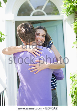 Couple hugging on front stoop - Stock Photo