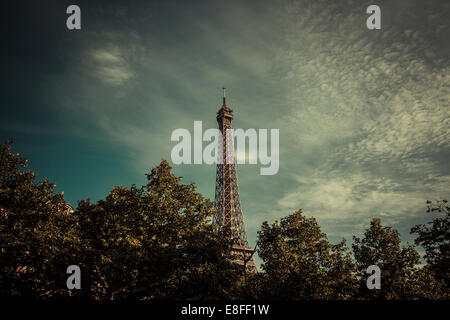 Eiffel Tower above treetops, Paris, France - Stock Photo