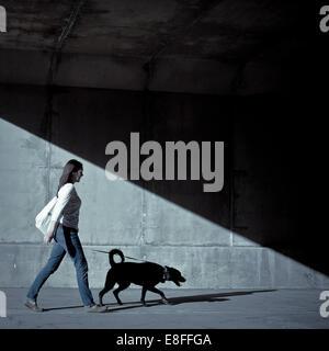 Woman walking with dog under bridge - Stock Photo