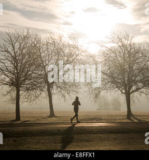 Silhouette of a woman Running through the park, England, UK - Stock Photo