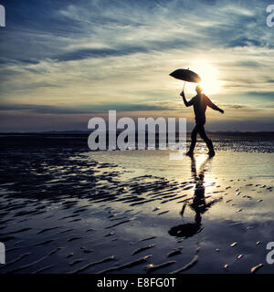 Man walking with umbrella - Stock Photo
