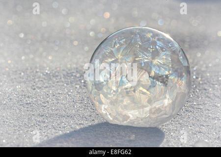 Frozen soap bubble on ice - Stock Photo