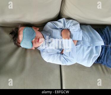 Boy lying on sofa and wearing sleeping eye mask - Stock Photo