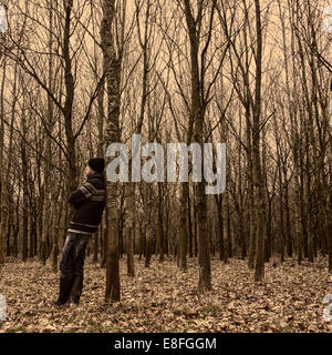Man standing in forest leaning against a tree - Stock Photo